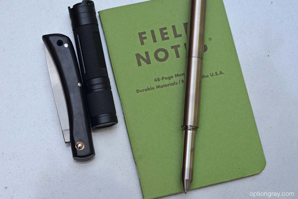 field notes with pen, pocket knife, and flashlight