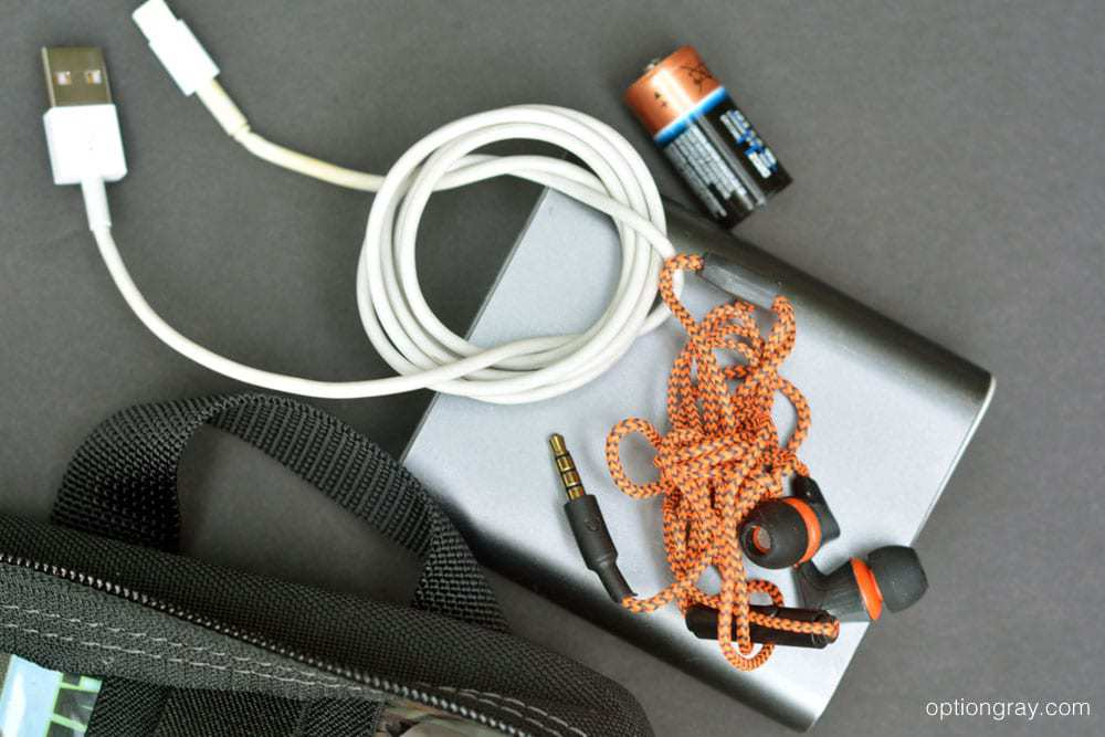 spare battery, phone charger, ear buds, and battery bank