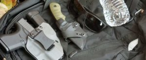 glock 43 in alex and ryan design master blaster holster, with boker ridgeback fixed blade knife, sunglasses, and a bottle of water.