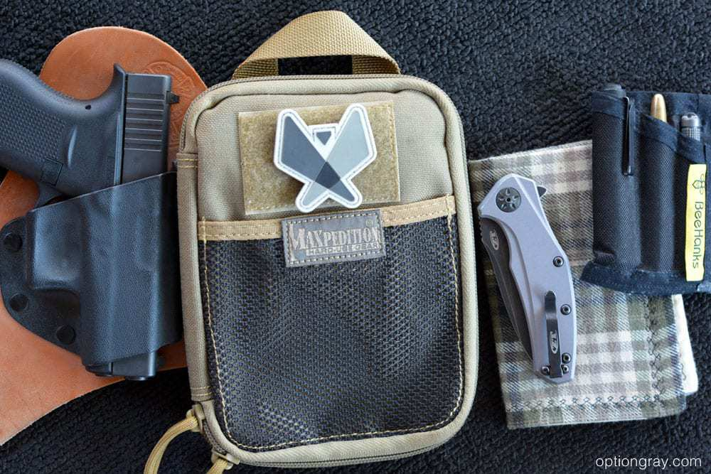 glock handgun in crossbreed holster, maxpedition edc organizer pouch, zero tolerance knife, flashlight, pen, and firestarter in pocket organizer, and a handkerchief.