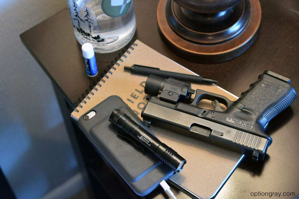 handgun with weapon mounted light, handheld flashlight, pen, notebook, water bottle, and chapstick on a nightstand.