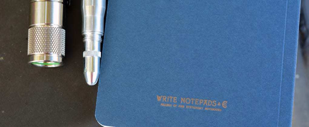 everyday carry gear including a bullet pencil, pocket notebook, and flashlight