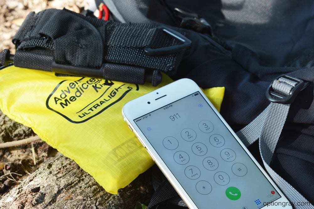 emergency call on cell phone with first aid kit and tourniquet.