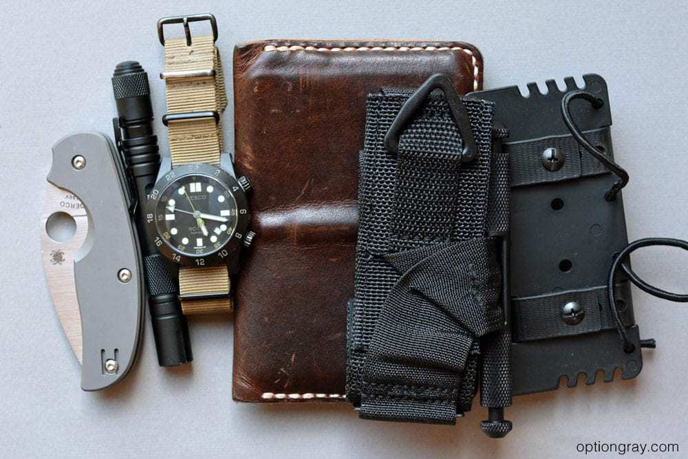 EDC gear including a pocket knife, pen flashlight, resco watch, notebook wallet, phlster flatpack, tourniquet.