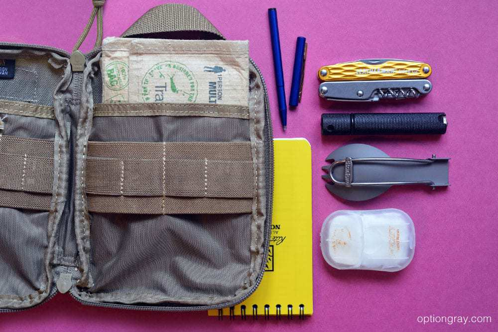 """A Maxpedition E.D.C. Organizer in khaki holds an Adventure Medical Kit Travel Medic, Rite in the Rain 3"""" x 5"""" Notebook in yellow, Fisher Space Pen Stowaway Pen in blue, Leatherman Juice C2 in yellow, Solo Scientific Aurora Firestarter, Vargo Titanium Folding Spork and Sea to Summit Pocket Hand Wash."""