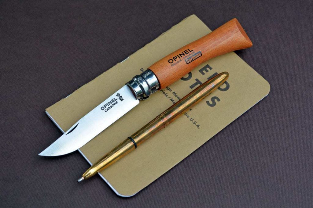 Opinel No 7 Carbon/Beech, Fisher Space Pen Bullet Pen Raw Brass, and Field Notes Original.