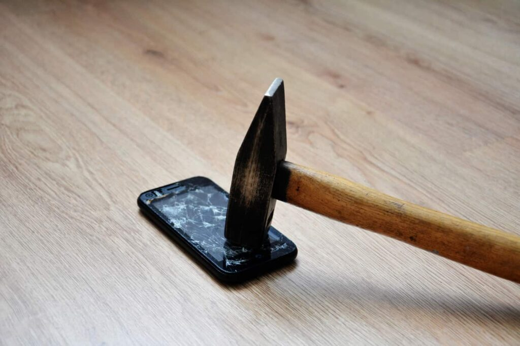 Broken mobile phone screen with a big black iron hammer. LCD screen broken, cracked and unusable smart phone. Hammer Smashing Cellular Phone.
